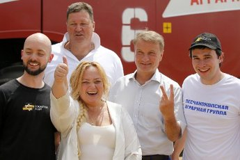 ROSTOV REGION, RUSSIA - JULY 16, 2020: Cognitive Pilot General Director Olga Uskova (2nd L) thumbs up and Sberbank CEO German Gref (2nd R) makes a V-sign as they pose for a photograph after an event to demonstrate operation of a Torum 750 unmanned