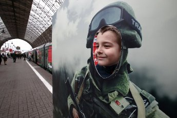 MOSCOW, RUSSIA - APRIL 25, 2021: A child poses for a photo by a themed train of the military patriotic campaign âWe Are the Army of the Country! We Are the Army of the People!â at the Kiyevsky railway station. For the next 64 days, the train