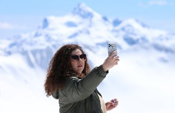 REPUBLIC OF KABARDINO-BALKARIA, RUSSIA â MAY 6, 2021: A woman takes a selfie at the Elbrus year-round resort in the Caucasus Mountains. Yelena Afonina\/TASS