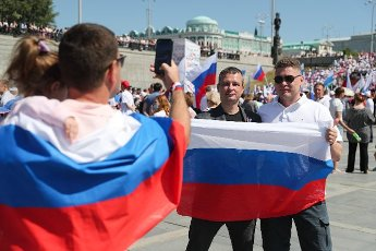 YEKATERINBURG, RUSSIA - JUNE 12, 2021: People pose for a photo with the Russian flag during celebrations of Russia Day in the Istorichesky [Historical] public garden. Donat Sorokin\/TASS