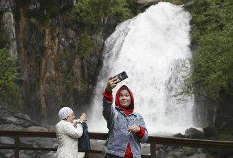 REPUBLIC OF ALTAI, RUSSIA â JUNE 13, 2021: A girl takes a selfie by the Korbu Waterfall on the Bolshaya Korbu River flowing into Lake Teletskoye. Kirill Kukhmar\/TASS