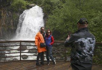 REPUBLIC OF ALTAI, RUSSIA â JUNE 13, 2021: Tourists pose for a photo by the Korbu Waterfall on the Bolshaya Korbu River flowing into Lake Teletskoye. Kirill Kukhmar\/TASS