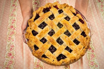Close-up of hands holding freshly baked blueberry pie