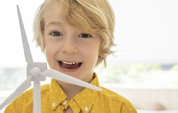 Portrait of smiling boy (6-7) with wind turbine model