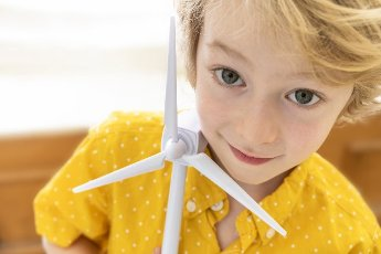 Portrait of boy (6-7) with wind turbine model