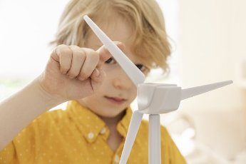 Boy (6-7) playing with wind turbine model