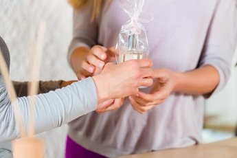Close-up of woman\'s giving perfume gift to her friend