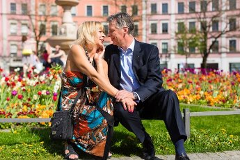 Mature or senior couple sitting on a bench during spring in the city and enjoy the sun