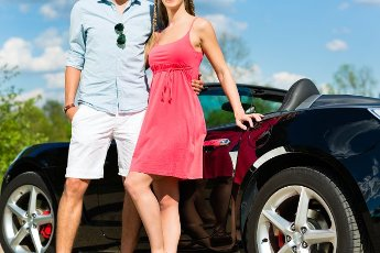Young hip couple - man and woman - with cabriolet convertible car in summer on a day trip