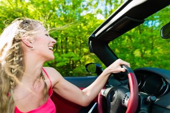 Young beautiful woman with cabriolet convertible car in summer on a day trip