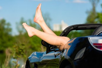 Young woman hanging her legs over the door of her cabriolet