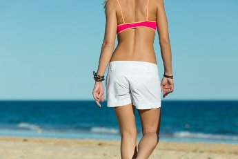 The back of a young woman on the beach in the sand, they goes to the water, probably she has vacation