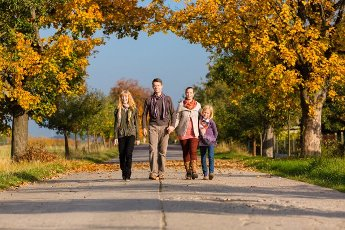 Young family with Mother, father and daughters walking through colorful trees in fall or autumn