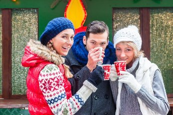 Man and two women or a friends drinking during advent season or holiday a mug of spiced wine or eggnog or punsch on the Christmas or Xmas market
