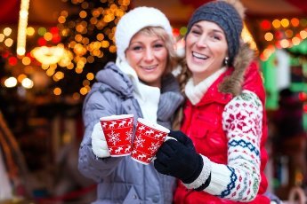 Two women friends drinking during advent season in front of a carousel a cup or mug of spiced wine or eggnog or punsch on Christmas or Xmas market
