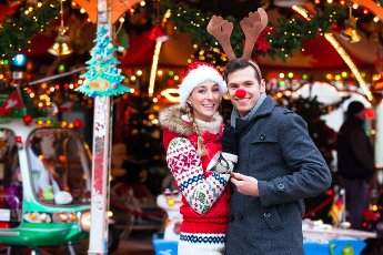 """Man and woman or a couple or friends during advent season or holiday in front of a carousel or """"marry-go-round"""" on the Christmas or Xmas market"""