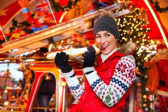 Woman eating during advent season or holiday in front of a carousel or marry-go-round a grilled sausage with bun on the Christmas or Xmas market