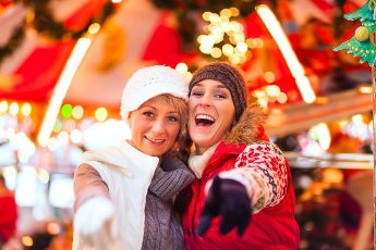 Two women or friends during advent season or holiday in front of a carousel or merry-go-round on the Christmas or Xmas market