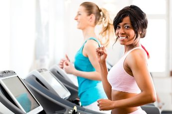 Running on treadmill in gym or fitness club - two women exercising to gain more fitness