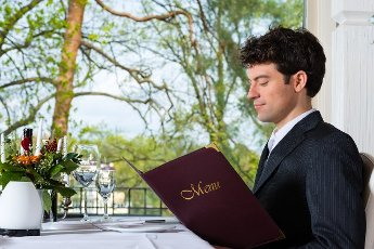 Man or Businesspeople having business lunch in a fine dining restaurant and choose in the menu