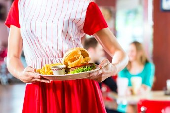 Friends or couple eating fast food and drinking milk shakes on bar in American fast food diner, the waitress wearing a short costume