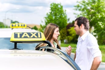 Young woman and driver standing together in front of taxi, she has reached her destination