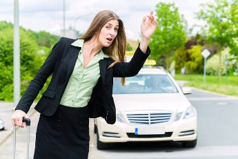 Young businesswoman waiting for a taxi stopping the driver waving from the sidewalk