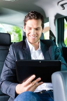 Young businessman traveling in taxi, he using the tablet computer for emails