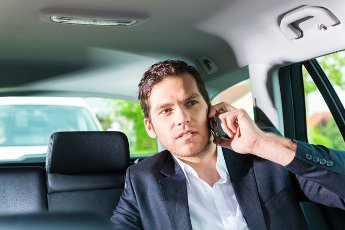Young businessman traveling in taxi, he is busy on the phone