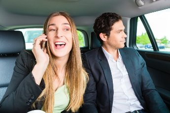 Young businesspeople traveling in taxi, she is busy on the phone, they are colleagues