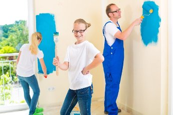 Father and his daughters or daughter with her friend are painting with paint roller a wall in blue