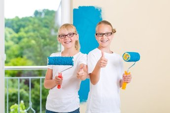 In Family home girl with her sister or friend painting with paint roller a wall in blue