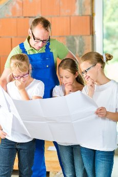Father and kids or daughters and friends looking at a construction plan on a building site