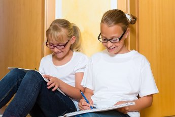 Girls or Sisters doing homework together at home for school next day