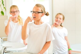 Children, Sisters or daughter with friends are brushing teeth or tooth at the washbasin