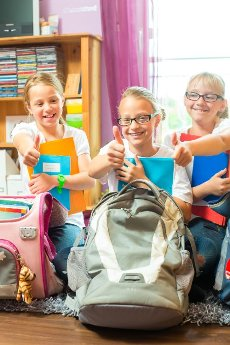 Girls or Sisters packing schoolbags with text books for school next day