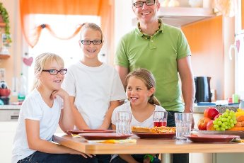 Family, father and children or daughter with friends in the kitchen at the table eating healthy fruits