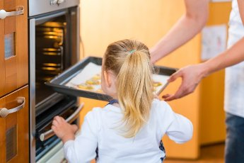 Mother and daughter baking cookies in the oven at home