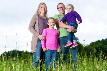 Mother, father and kids or daughter and friend standing outdoor on grass meadow