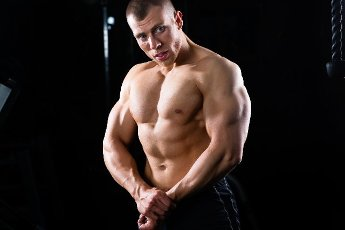 Strong man, bodybuilder posing in Gym, dumbbells are in the background