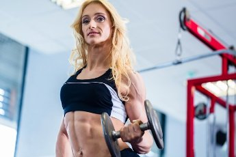Bodybuilder woman lifting weights in fitness gym