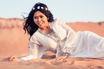 Woman laying in sand of Arabian desert