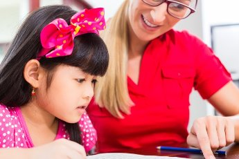 English private teacher helping Asian girl with homework