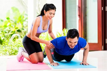 Asian woman helping man with push-up to gain better fitness