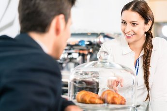 Friendly waitress looking at the client while pointing to French croissants in the coffee shop