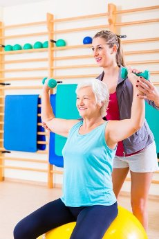 Senior woman with trainer doing fitness sport in gym