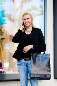 Mature woman with bags shopping in city using phone in front of shop window
