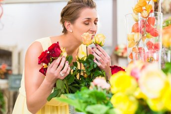 Florist woman smelling at roses enjoying the scent