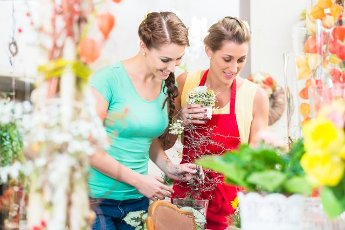 Florist woman and customer in flower shop discussing the offerings