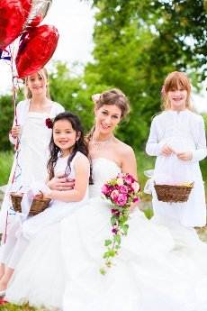 Wedding couple bride with flower children or bridesmaid in white dress and flower baskets